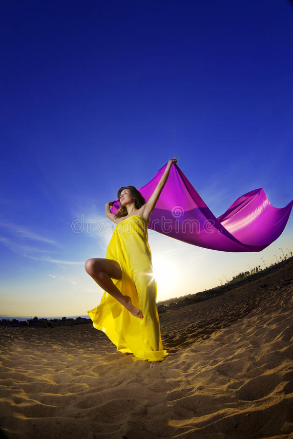 Girl at the beach on a background of the sun. The image of a beautiful girl at the beach growing tissue on a background of the sun stock photo