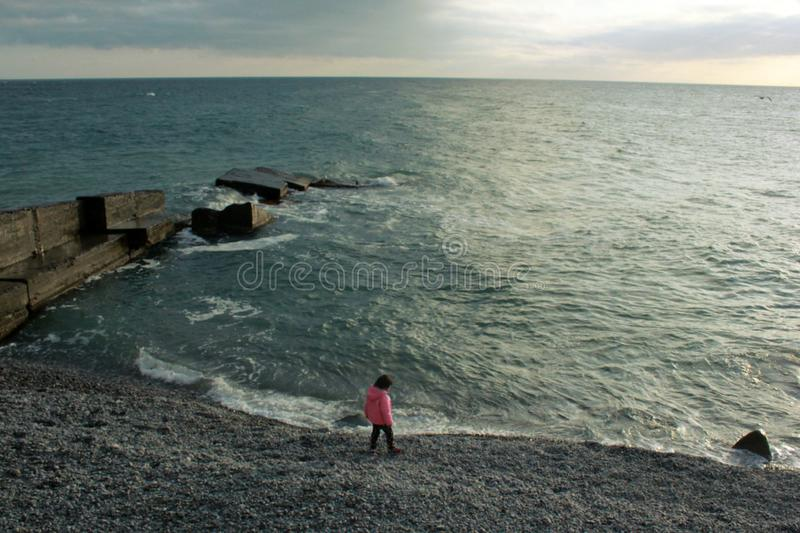 Girl on the beach, child, in a pink jacket, children play stock photos