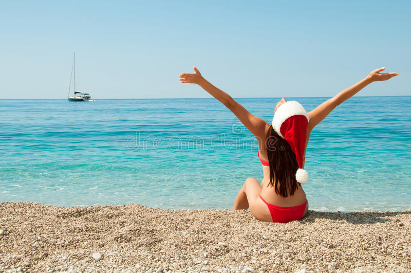 Girl on the beach in a Christmas hat stock images