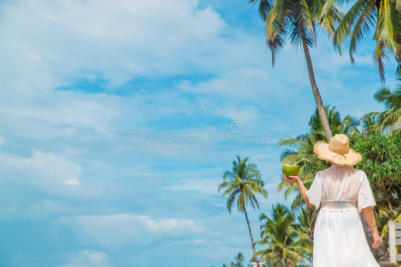 Girl on the beach drinks coconut. Selective focus stock photography