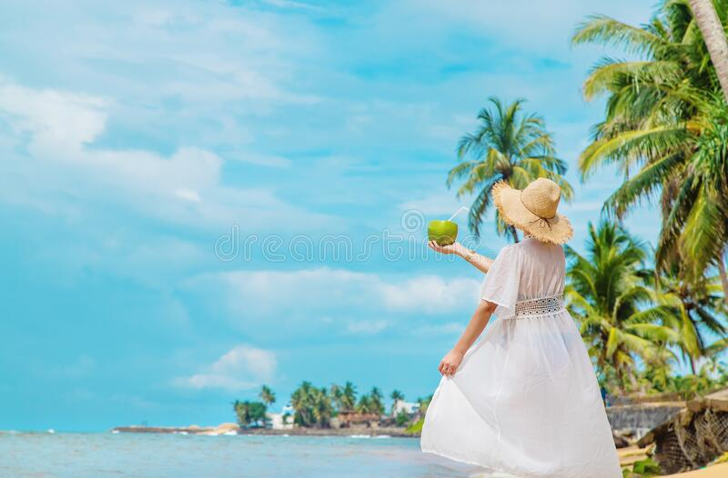 Girl on the beach drinks coconut. Selective focus royalty free stock photo