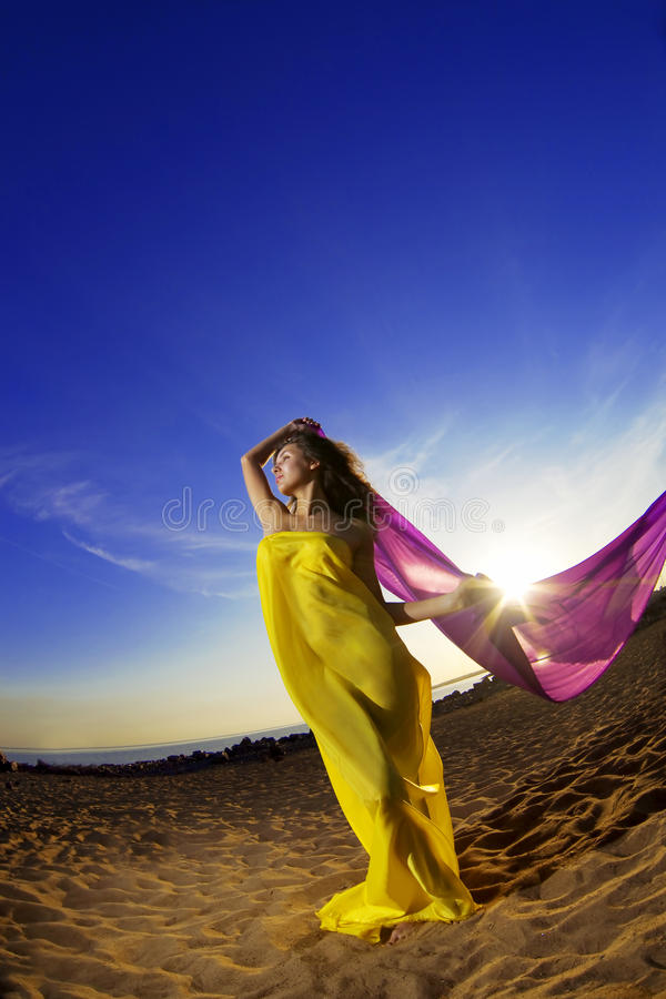 Girl at the beach growing tissue. The image of a beautiful girl at the beach growing tissue on a background of the sun royalty free stock photo