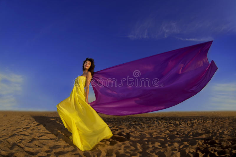 Girl at the beach growing tissue. The image of a beautiful girl at the beach growing tissue on a background of the sun stock photos