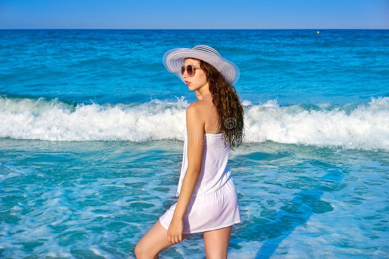 Girl with beach hat in sea shore profile. View with summer white dress royalty free stock photo