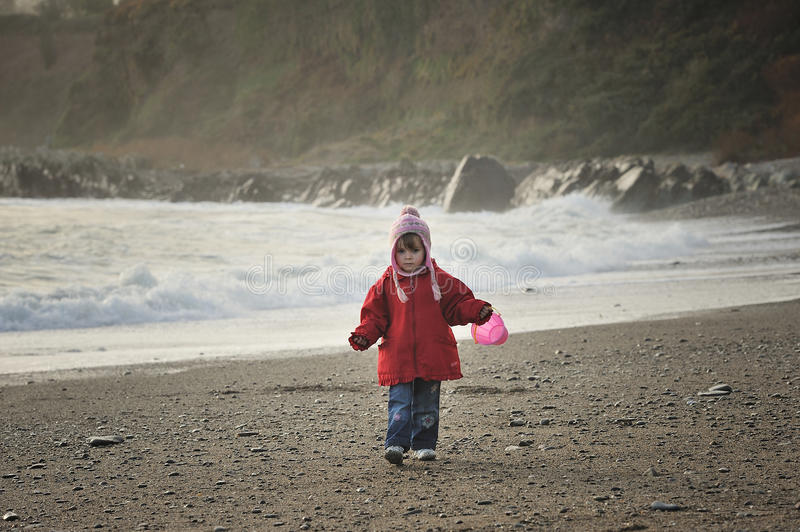 Girl on a Beach. Little girl with a pink bucket on the beach royalty free stock photography