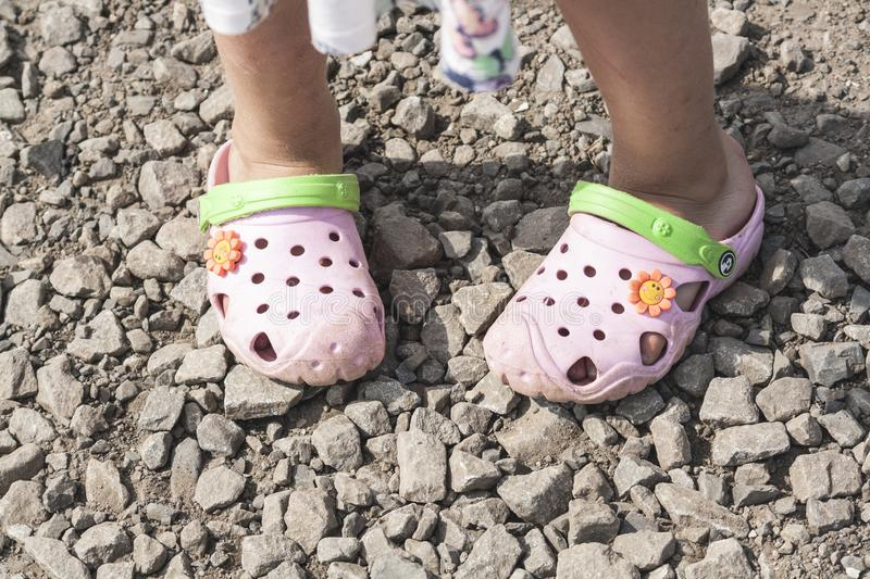 Girl in beach slippers crocs on a stone road royalty free stock image
