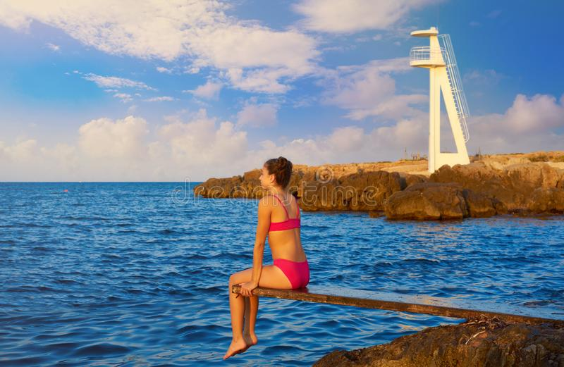 Girl at beach sunset on trampoline royalty free stock photography