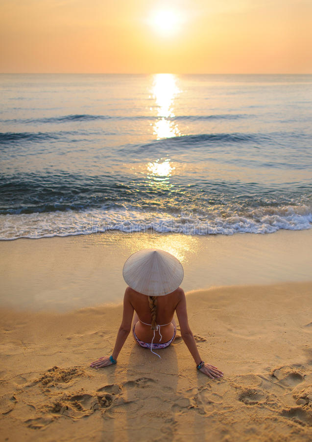 girl on beach at sunset wearing rice hat 3 stock photography