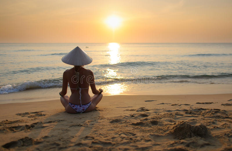 Girl on beach at sunset wearing rice hat 4 royalty free stock photography
