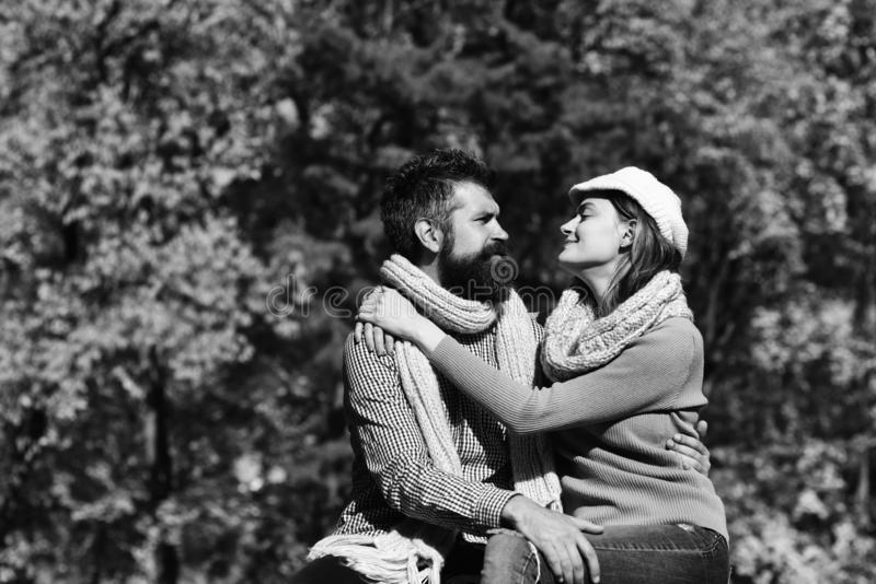 Girl and bearded guy or happy lovers on date hug. Girl and bearded guy or happy lovers on a date hug. Couple in love with scarves sits in park. Man and women royalty free stock photography