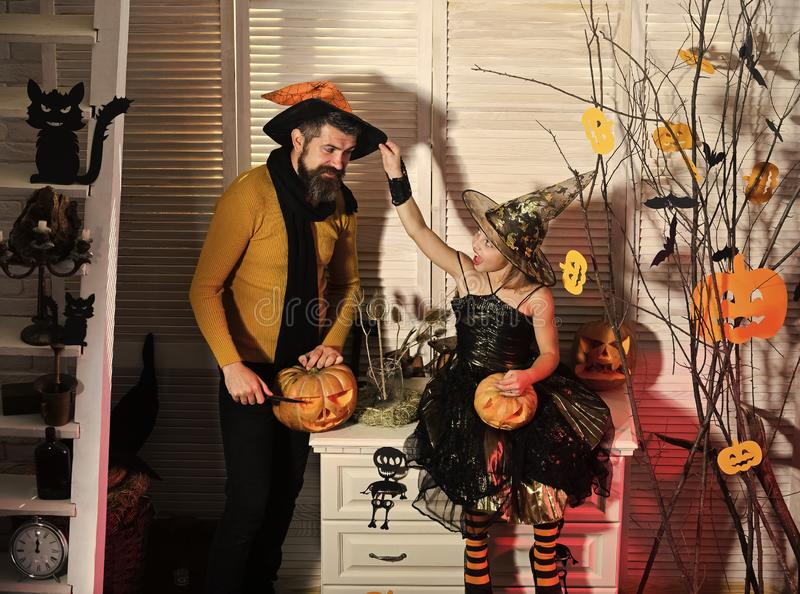Girl and bearded man with cheerful faces in carnival room. Girl and bearded men with cheerful faces on spooky carnival room background. Halloween party concept stock images