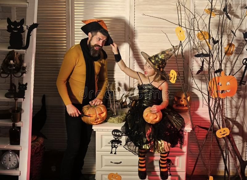 Girl and bearded man with cheerful faces in carnival room. Girl and bearded men with cheerful faces on spooky carnival room background. Halloween party concept royalty free stock photo