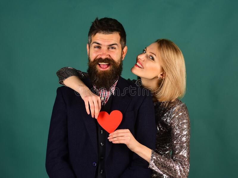 Girl and bearded man with happy faces play with heart. royalty free stock photo