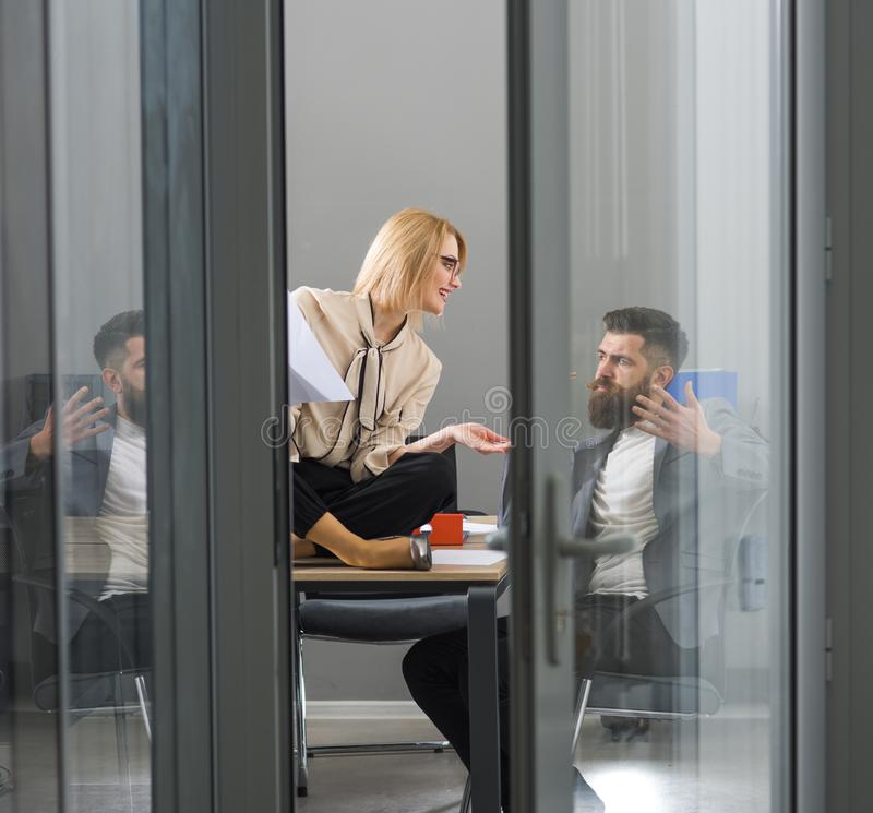 Girl and bearded man work together in office. Girl and man write business plan, collaboration for success. Girl and bearded men work together in office. Girl and stock images