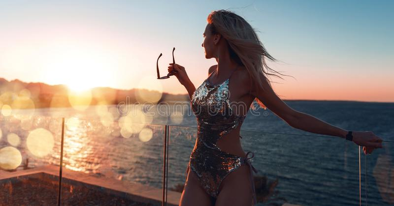 Girl in a beautiful bathing suit at sunset by the sea holding sunglasses royalty free stock photography