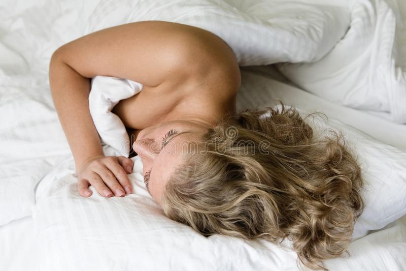 The girl with beautiful hair sleeps in bed. stock image