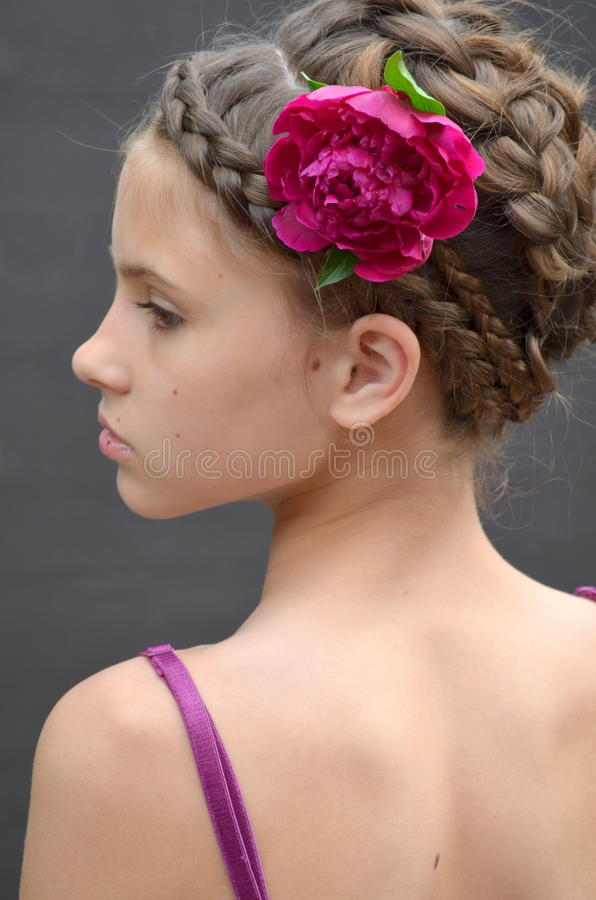 The girl in a beautiful hairstyle. With pink peony royalty free stock photo