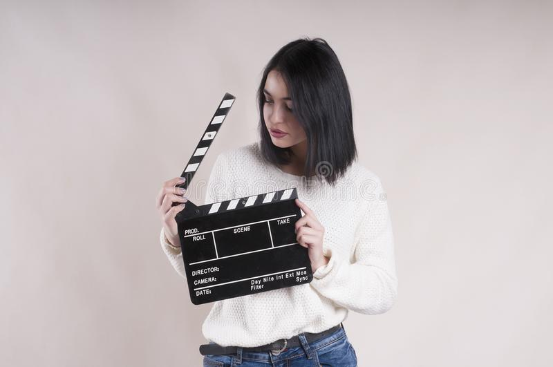 Girl beautiful is holding a clapperboard and posing. Girl is holding a clapperboard and posing beautiful royalty free stock images