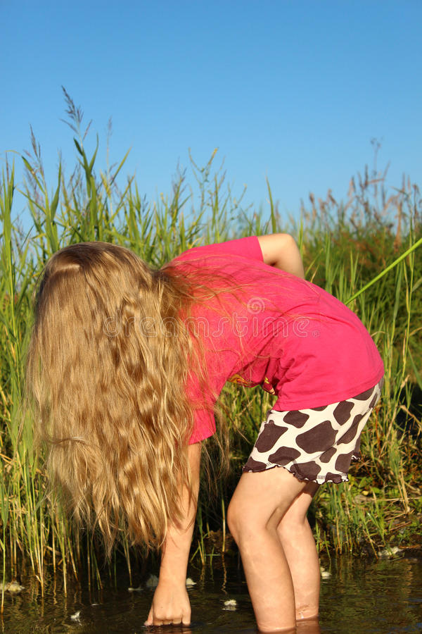 Girl with beautiful long golden hair on the shore of the lake royalty free stock photos