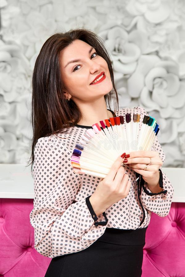 A girl with a beautiful manicure, holding samples of manicure and smiling. Brunette royalty free stock image