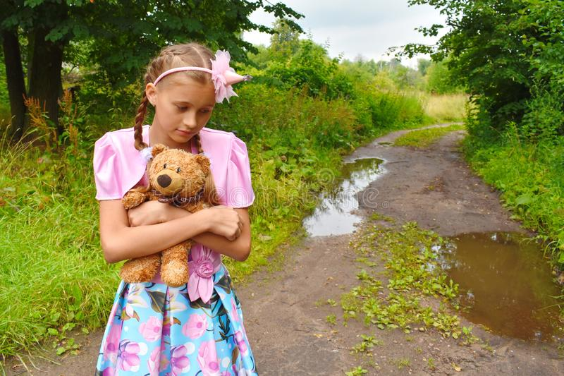 Girl in a beautiful pink ball dress with a teddy bear. Girl the princess keeps a toy in a garden in the summer stock images