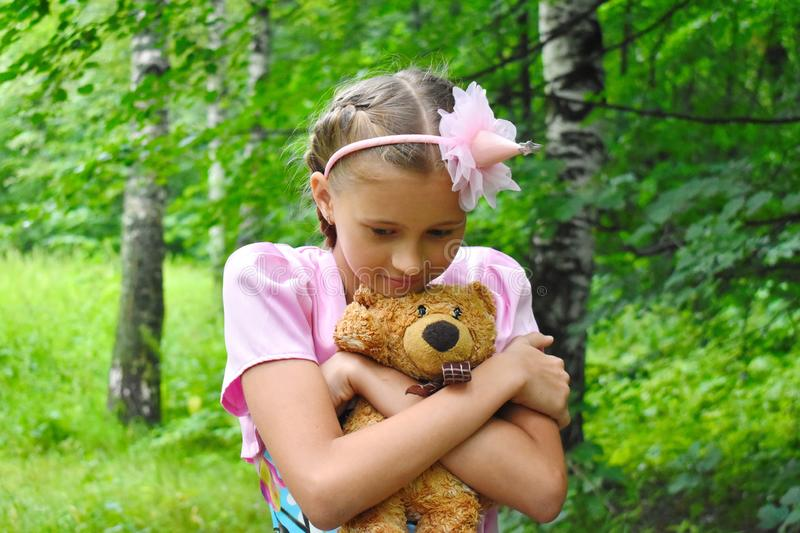 Girl in a beautiful pink ball dress with a teddy bear. Girl the princess keeps a toy in a garden in the summer royalty free stock photo