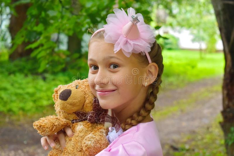 Girl in a beautiful pink ball dress with a teddy bear. Girl the princess keeps a toy in a garden in the summer royalty free stock image
