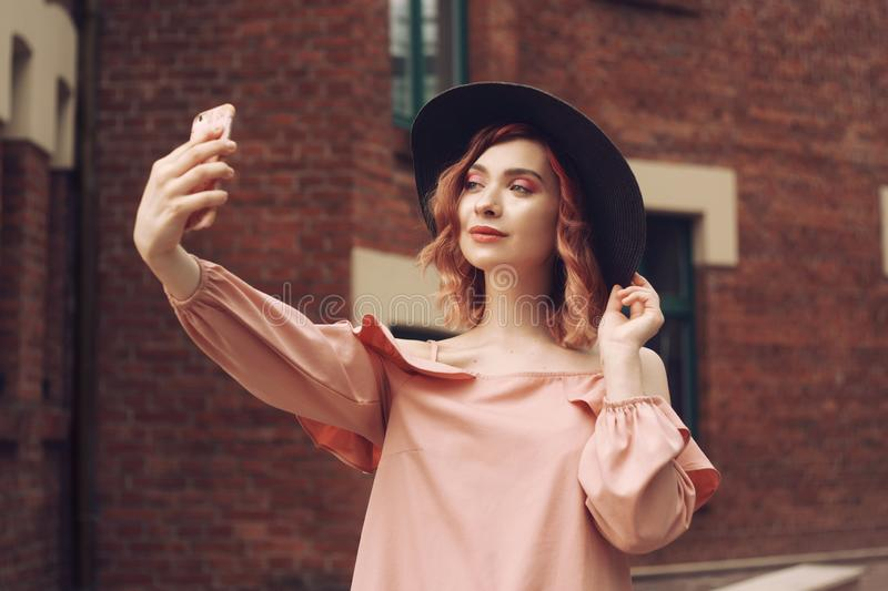 Girl in a beautiful pink dress and black hat. The girl with pink curly hair travels. A girl makes a photo on a smartphone. royalty free stock images