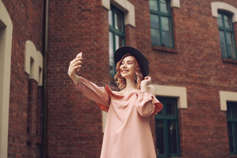 Girl in a beautiful pink dress and black hat. The girl with pink curly hair travels. A girl makes a photo on a smartphone. royalty free stock photos