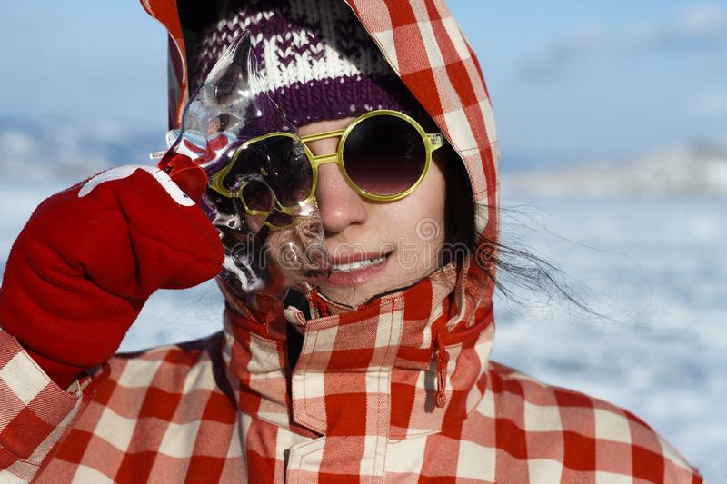 A girl with a beautiful radiant smile in sunny yellow glasses and red mittens is holding an icicle from Lake Baikal. royalty free stock images