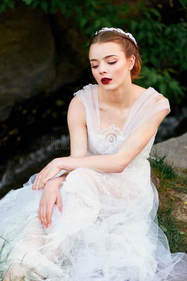 Girl in a beautiful white lace dress straightens her . Boho style. Girl in a beautiful white lace dress straightens her dress. Ballerina. Boho style stock images