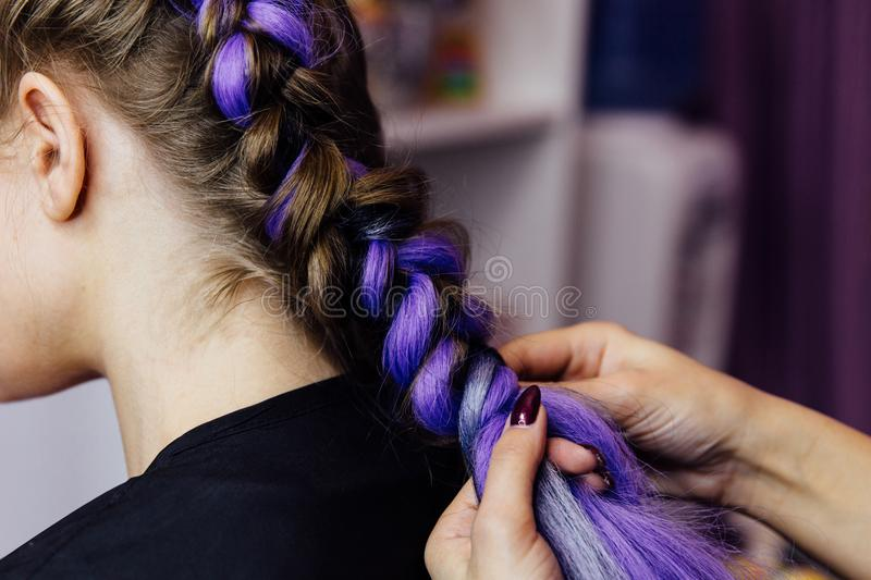 Girl in the beauty salon is weaved with braids. braided pigtails. Girl in the beauty salon hairdresser is weaved with braids. braided pigtails. Braiding with stock images