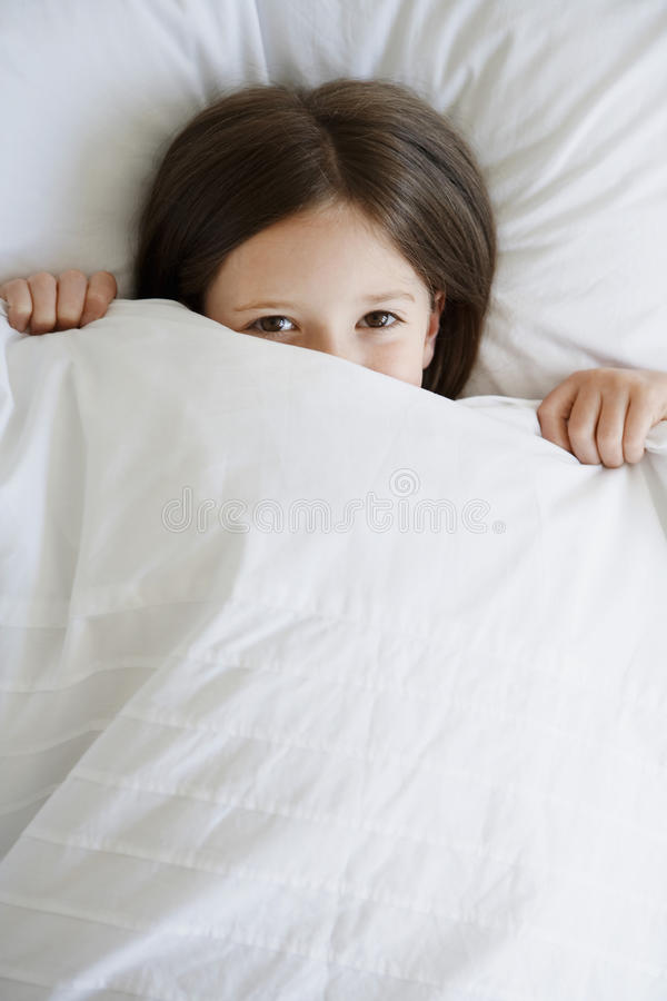 Girl In Bed Pulling Blanket Over Face. High angle portrait of little girl in bed pulling blanket over face royalty free stock images