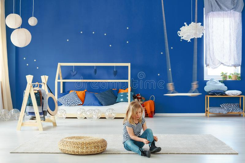 Girl bedroom with blue wall. Swing, clothes rack and bed royalty free stock image