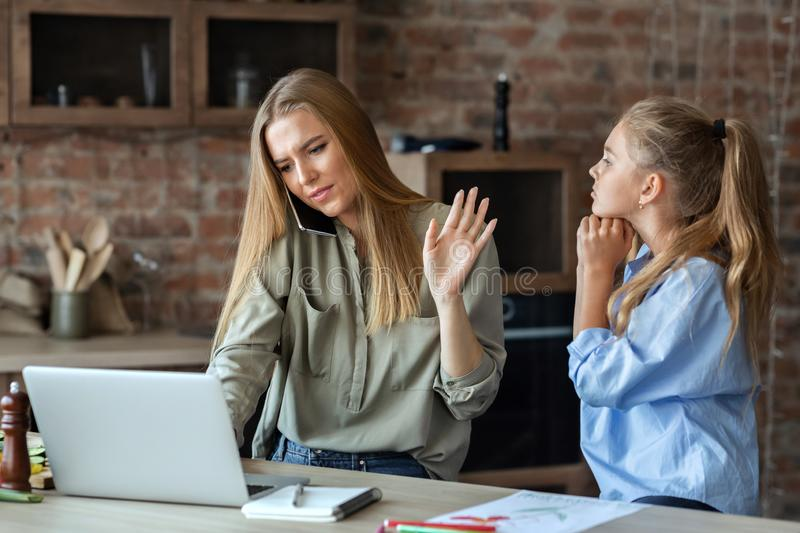 Girl begging her busy mom for attention. Little daughter asking her mom for attention, busy mother talking by phone and looking at laptop, kitchen interior, copy royalty free stock images