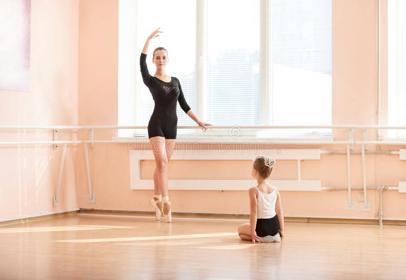 Girl beginner watching classmate standing en pointe. In ballet dancing class royalty free stock photos
