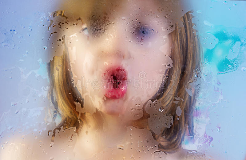Girl behind a dewy glass stock photography