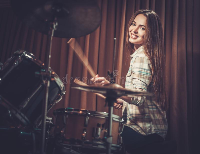 Girl behind drums on a rehearsal. Young cheerful girl behind drums on a rehearsal stock photography