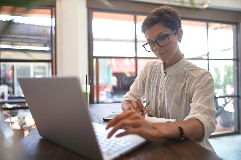 Girl working in a cafe. Freelance concept stock image
