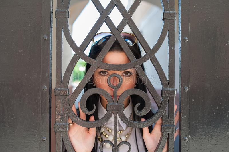The girl behind the metal door. Holding a metal fence. Young charming teenage girl with long hair with pleading eyes of mercy.  stock images