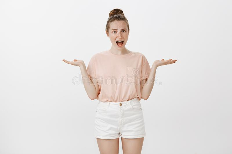 Girl being accused in making troubles standing questioned and offended over gray background, shrugging with spread hands royalty free stock images