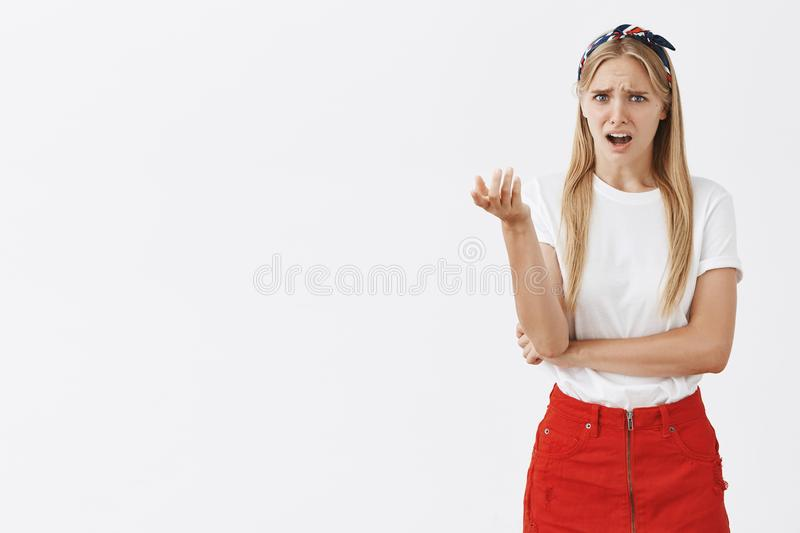 Girl being picky, looking what assistent offers her. Portrait of displeased moody and arrogant modern woman in headband. And skirt, pointing with disdain at stock image