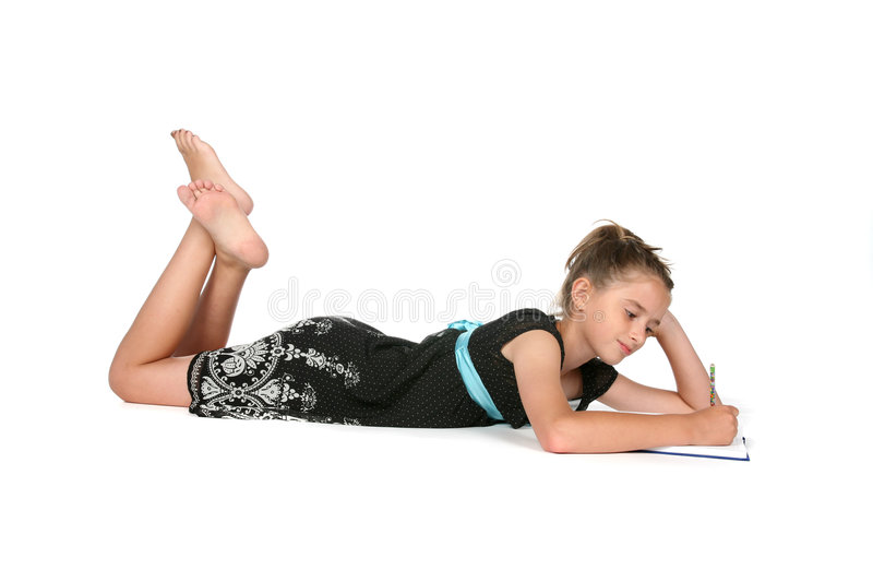 Girl on belly writing royalty free stock photo