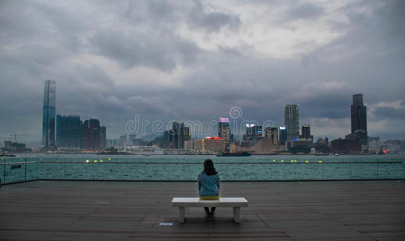 A girl on a bench looking at the Hong Kong skyline. royalty free stock photography