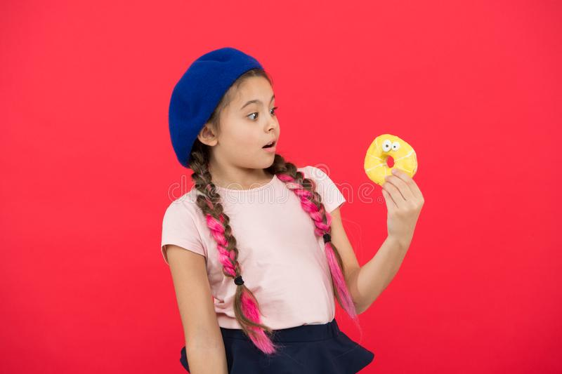 Girl in beret hat hold donut red background. Kid playful girl eat donut. Health and nutrition concept. Sweet life. Sweets shop and bakery concept. Kid fan of stock images