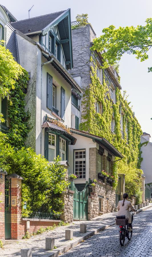 Girl on bicycle climbs up the cobblestone pavement of old Paris as she drives past green-filled houses royalty free stock photos