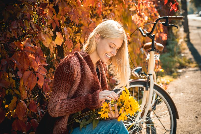 Girl with bicycle and flowers. Woman bicycle autumn garden. Active leisure and lifestyle. Autumn simple pleasures. Girl. Ride bicycle for fun. Blonde enjoy royalty free stock photography