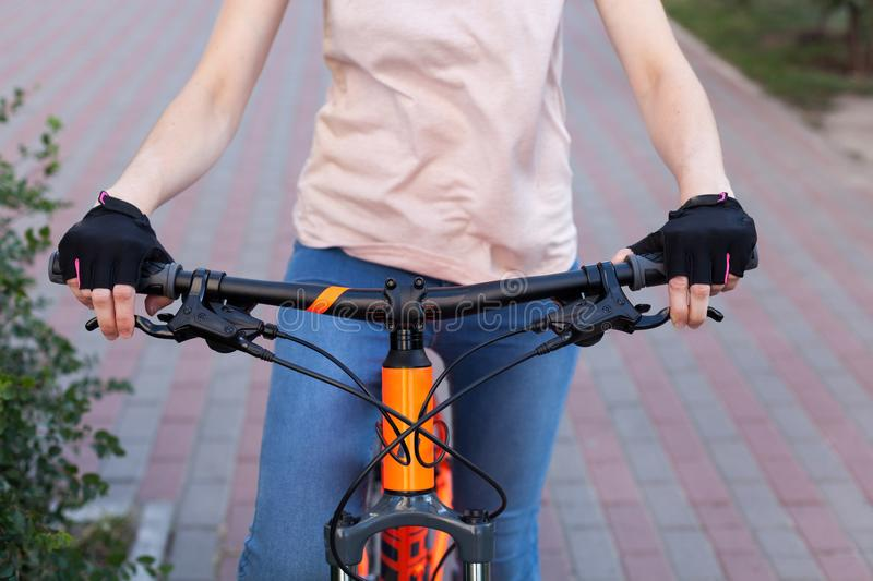 A girl in bicycle gloves holds her hand on the handlebars, clamping the brakes. A bicycle element on a street background. stock photo