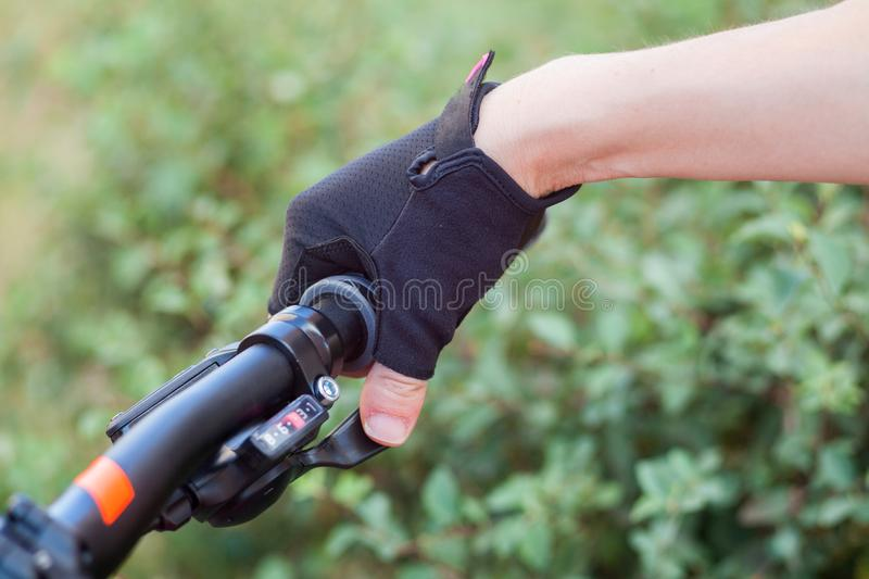A girl in a bicycle gloves holds her hand on the handlebars, switches speeds. royalty free stock image