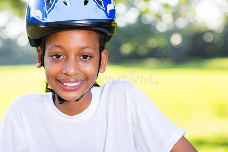 Girl bicycle helmet. Portrait of a young indian girl with bicycle helmet outdoors stock image
